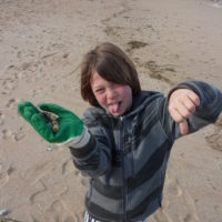 enfant surfeur nettoie plage cap ferret